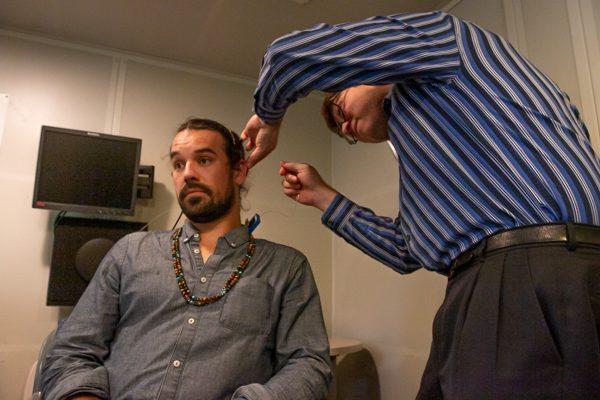 Dr. Kronen adjusts testing equipment on Nathan's head